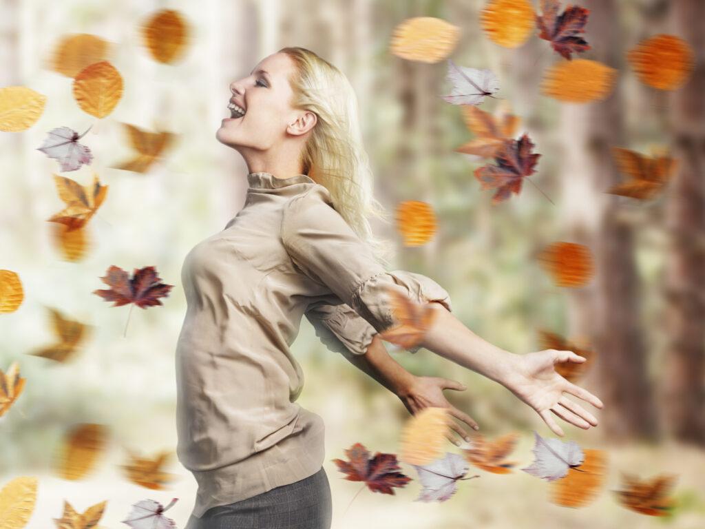 Eine Frau steht im Wald und breitet ihre Arme vor lauter Glück aus.